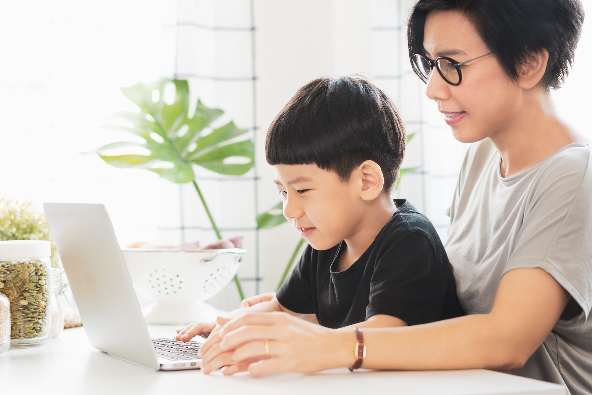 A mother accompanying a child in an online Chinese class