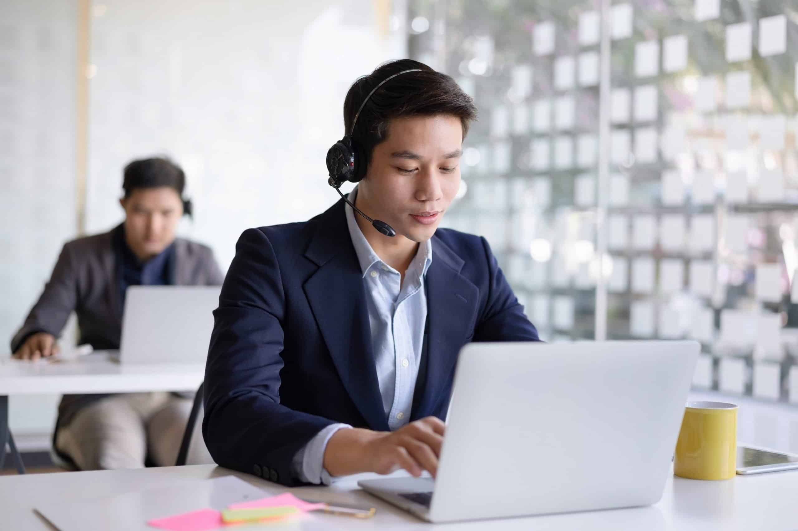 Attractive young asian male call center agent in headset consulting client