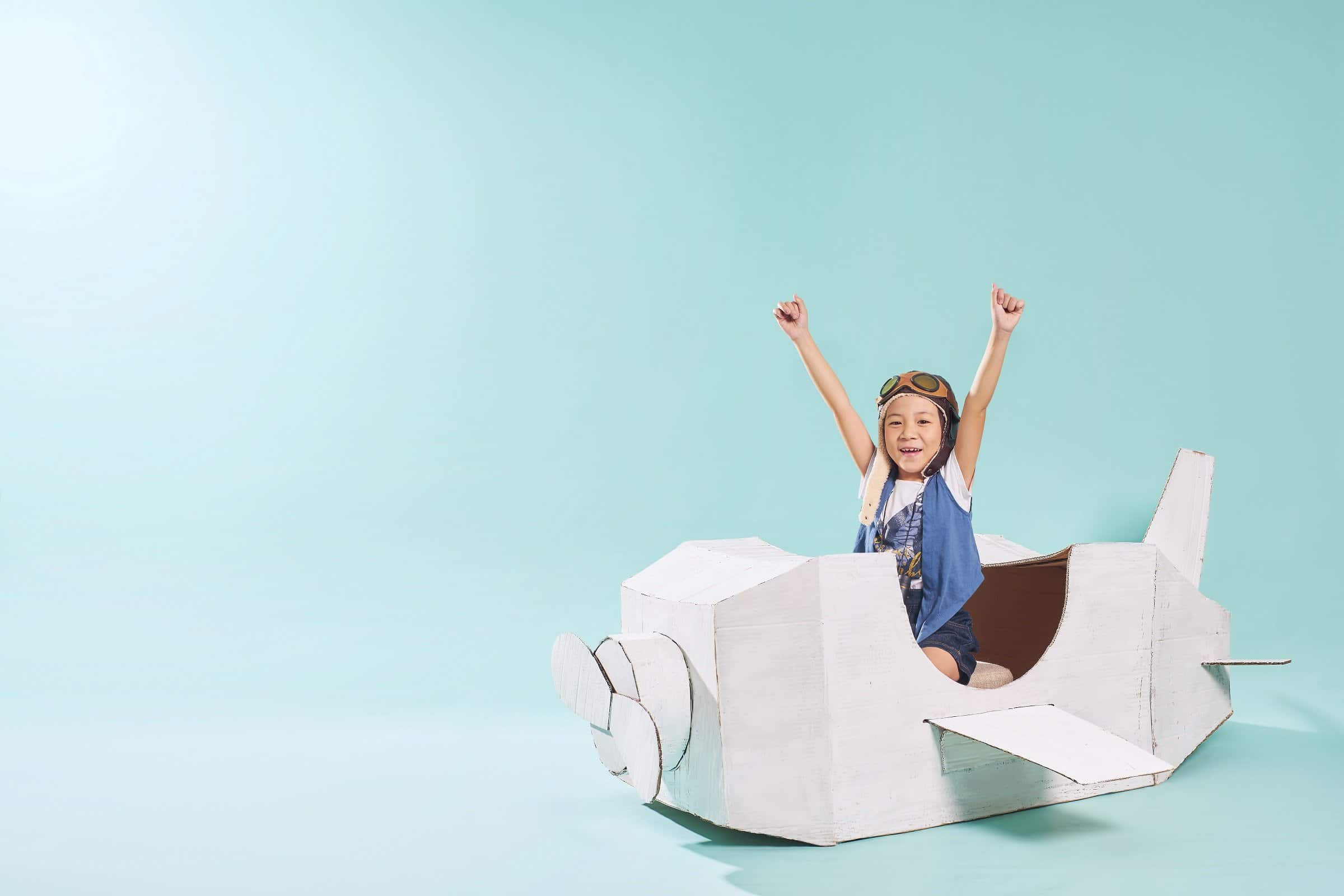 Little asian girl is happy sitting on a hand made cardboard paper plane . Isolated on mint green background