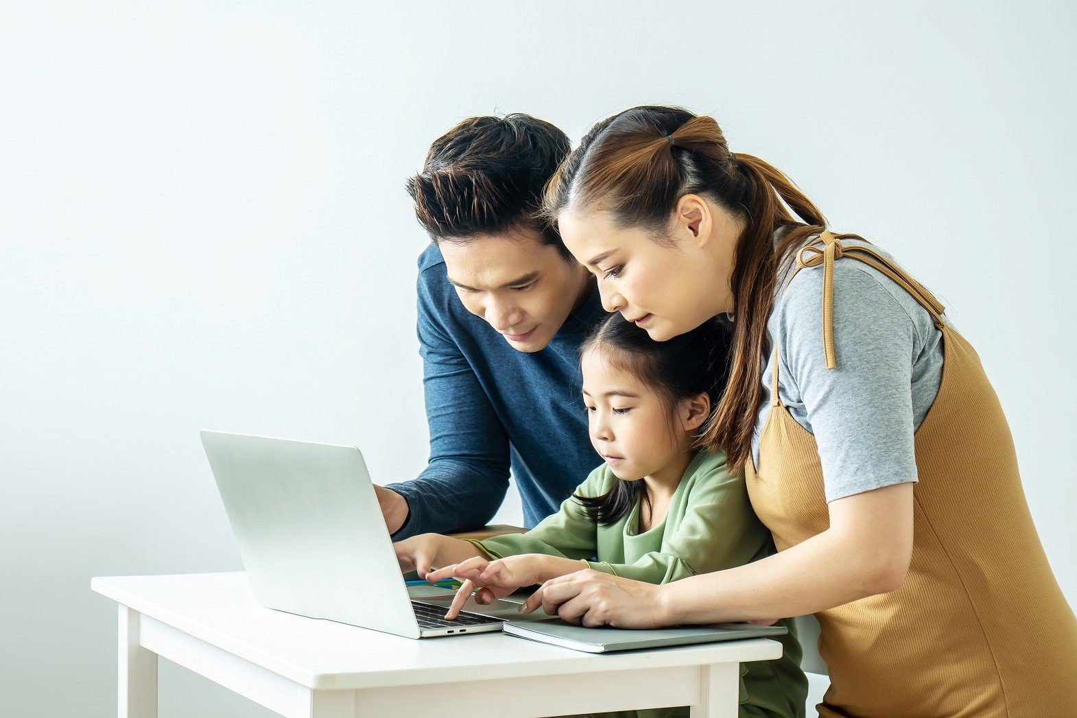 Happy young Asian family using at the laptop to surf internet together at home, , relaxing at home for lifestyle concept