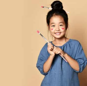 Cute smiling asian kid girl artist with painted red hearts on cheeks and with brush in hair and in hands over yellow wall background with copy space
